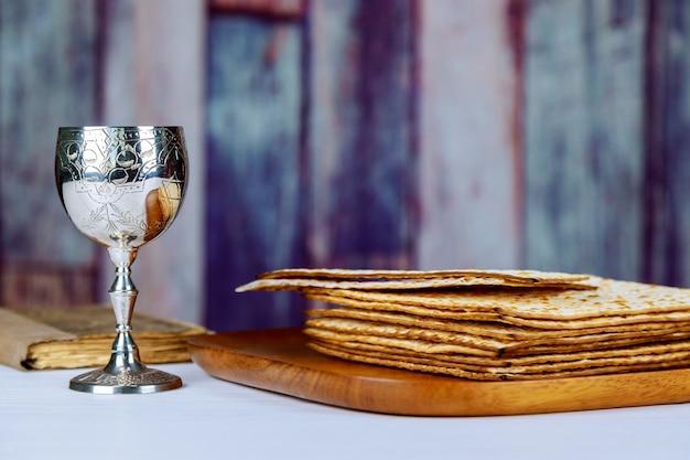 Vino rosso kosher con un piatto bianco di matzah o matzo e una haggada pasquale