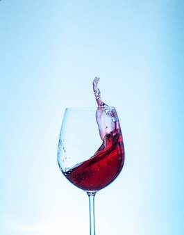 Vino rosso nel bicchiere su sfondo blu. il concetto di bevande e alcol.