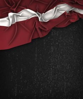Vintage bandiera della lettonia su una lavagna nera grunge con spazio per il testo