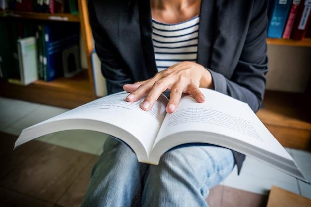 Vintage tono di asia donna lettura libro in libreria. retro effetto filtro, soft focus, bassa luce (attenzione selettiva)
