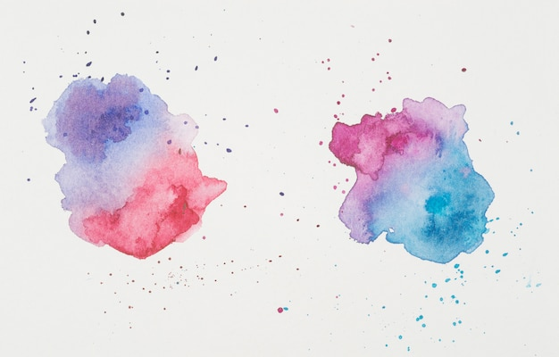 Viola e rosso vicino a macchie di lillà e acquamarina di vernici su carta bianca