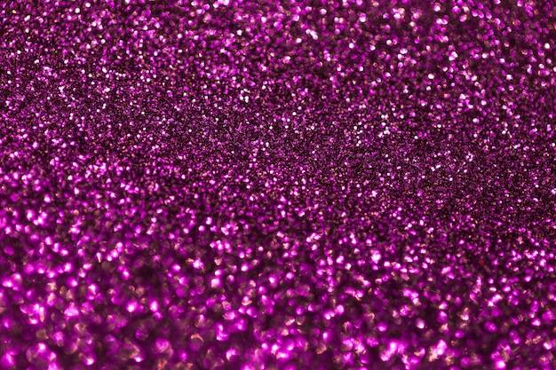 Viola scuro scintillante da piccole paillettes, primo piano. sfondo brillante.