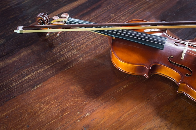 Violino d'annata con l'arco su fondo di legno, natura morta