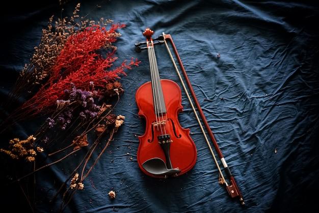 Violino e fiocco messi accanto a fiori secchi