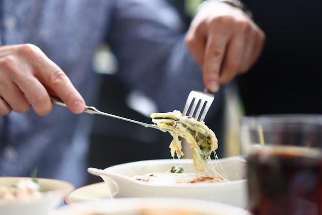 Visitatore bistrot seduto al tavolo tenendo forchetta e coltello con un pezzo di bolognese