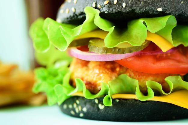 Vista a macroistruzione di gustoso hamburger nero con carne di manzo, formaggio, lattuga, cipolla, pomodori su sfondo blu.