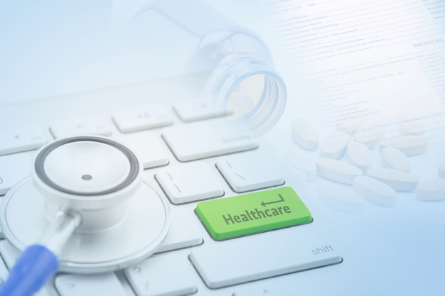 Vista a macroistruzione di uno stetoscopio sulla tastiera di computer e sul tasto botton con assistenza sanitaria con la pillola