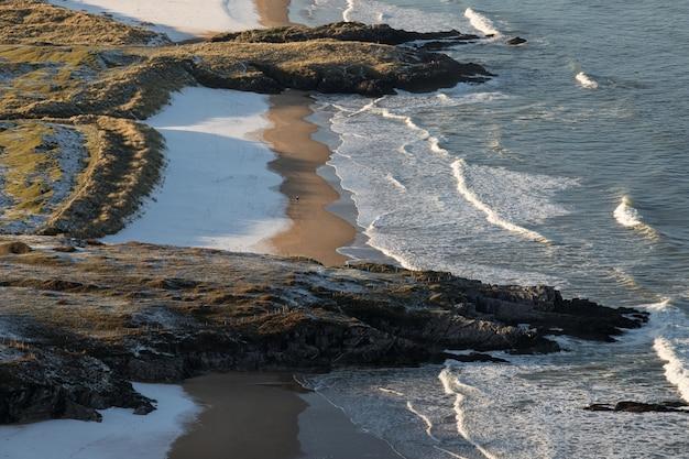 Vista a volo d'uccello delle onde che si infrangono sulla spiaggia con scogli sulla riva