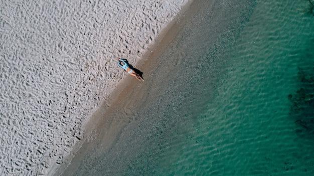 Vista aerea aerea giovane donna in bikini blu sdraiato sulla spiaggia di sabbia e onde, giovane donna prendere il sole e rilassarsi sulla spiaggia di sabbia bianca, viaggi estivi