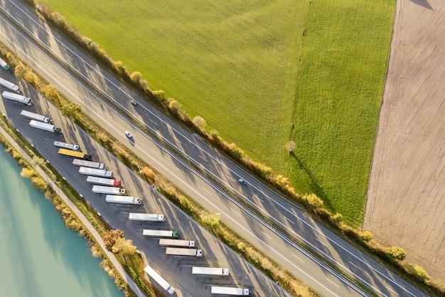 Vista aerea dall'alto verso il basso della strada da uno stato all'altro dell'autostrada con traffico rapido e parcheggio con i camion parcheggiati.