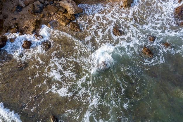 Vista aerea dall'alto verso il basso sopra le onde del mare e il litorale roccioso