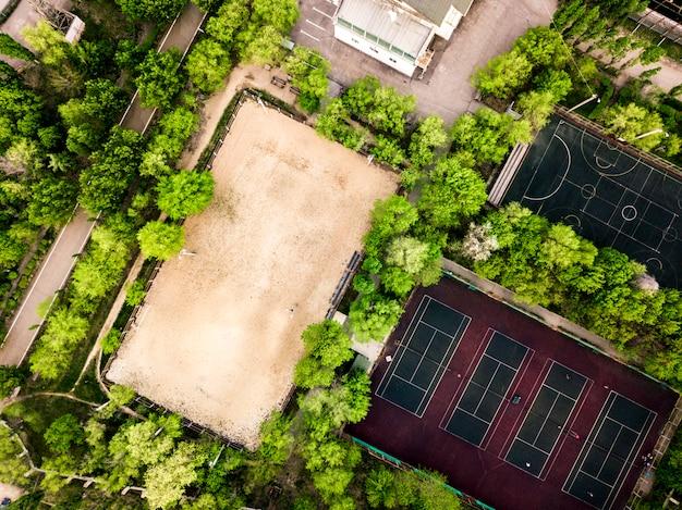 Vista aerea dei campi del campo di sport estivi e costruzione nella foresta