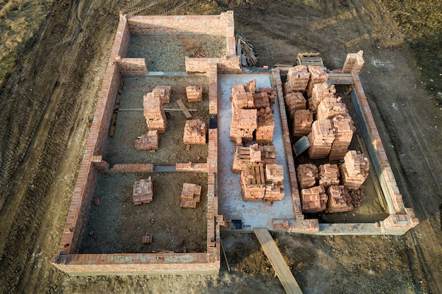 Vista aerea del cantiere. trincee scavate nel terreno e riempite di cemento come base per la futura casa, piano seminterrato in mattoni e pile di mattoni per la costruzione.