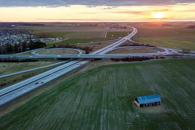 Vista aerea del granaio di legno nel campo verde su sfondo di autostrada moderna.
