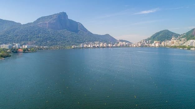 Vista aerea del lago rodrigo de freitas lagoon (lagoa) di acqua di mare nella città di rio de janeiro. puoi vedere la statua di cristo redentore sullo sfondo.