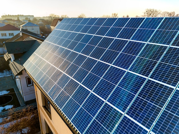 Vista aerea del nuovo moderno cottage a due piani con sistema fotovoltaico solare lucido blu sul tetto. concetto di produzione di energia verde ecologica rinnovabile.