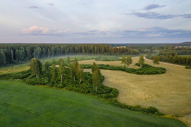 Vista aerea del paesaggio rurale lettone con campi agricoli, foreste e strade al tramonto