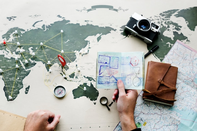 Vista aerea del passaporto della holding della mano che progetta il viaggio con la mappa