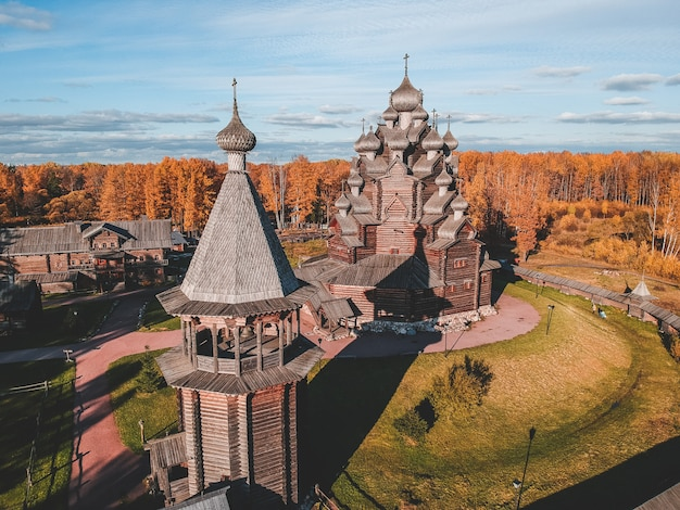 Vista aerea del teologo di legno della vecchia proprietà terriera della chiesa nella foresta di autunno. russia, san pietroburgo.