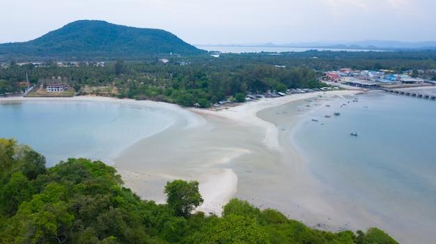 Vista aerea del tombolo con il molo e molti peschereccio nel mare vicino all'isola della roccia.