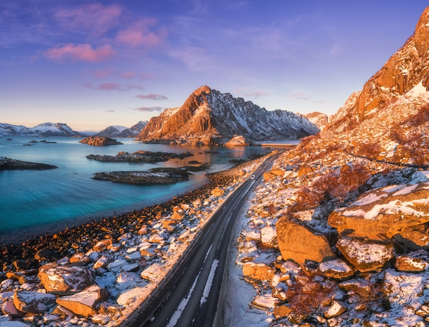 Vista aerea della bella strada di montagna vicino al mare, montagne, cielo viola al tramonto