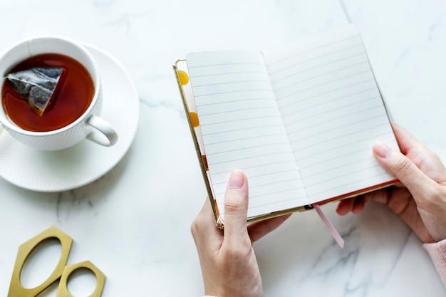 Vista aerea della bevanda e della donna calde del tè che tengono lo spazio in bianco della copia del giornale