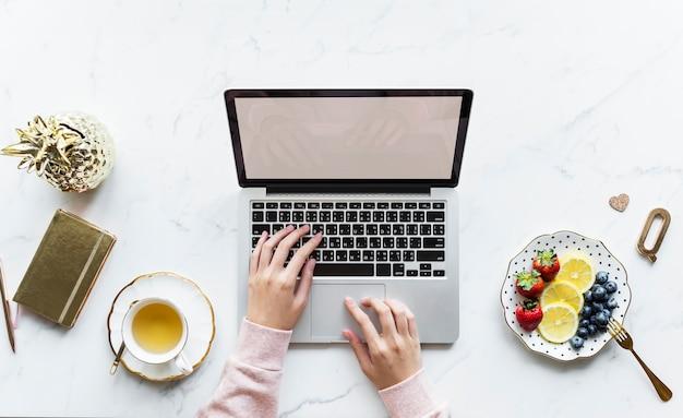 Vista aerea della donna che per mezzo di un computer portatile su un tavolo di marmo