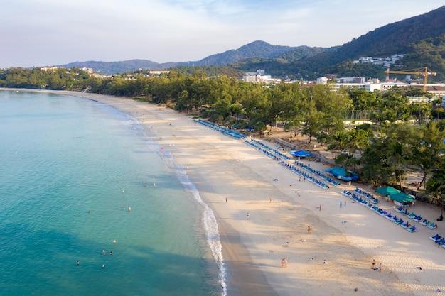 Vista aerea della gente che nuota nel mare trasparente del turchese alla spiaggia di karon a phuket, tailandia.