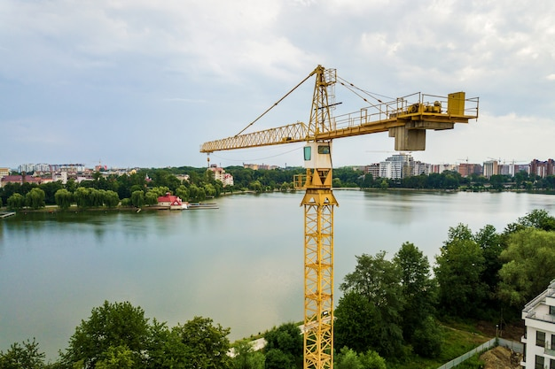 Vista aerea della gru di sollevamento della torre e della struttura di calcestruzzo dell'edificio residenziale dell'appartamento alto in costruzione in una città. sviluppo urbano e concetto di crescita immobiliare.