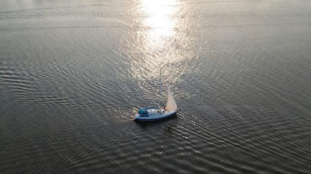 Vista aerea della navigazione dell'yacht nel fiume di dnieper sul tramonto da sopra