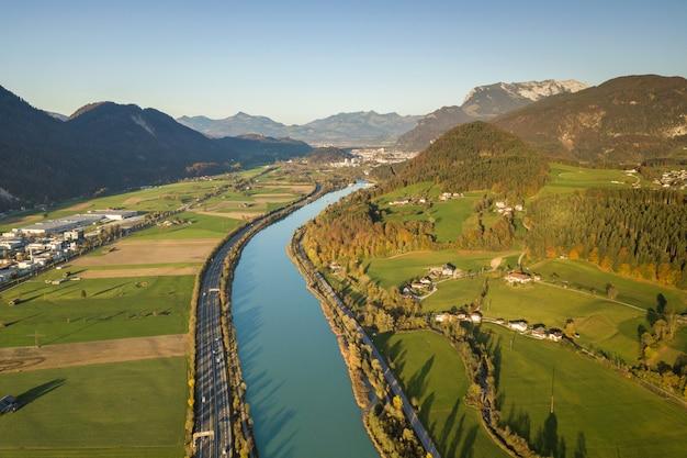 Vista aerea della strada da uno stato all'altro dell'autostrada con traffico rapido vicino al grande fiume in montagne delle alpi