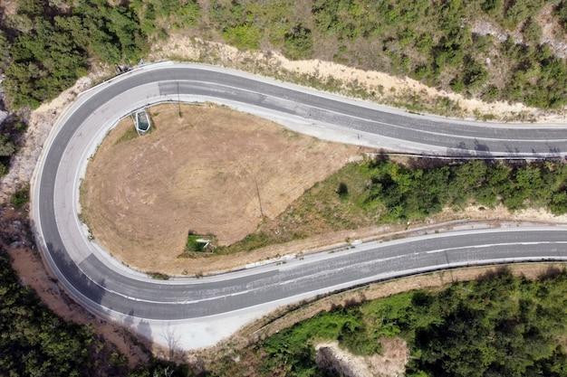 Vista aerea della strada tortuosa in legno di pino verde della depressione del passo di alta montagna.