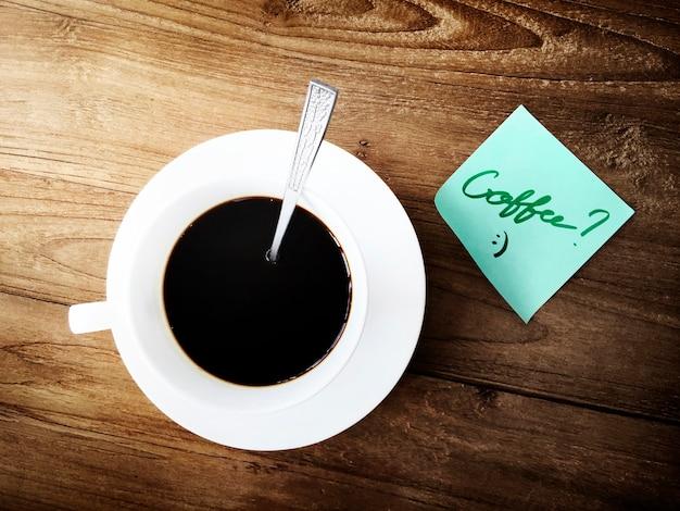 Vista aerea della tazza di caffè sulla tabella di legno con la nota appiccicosa