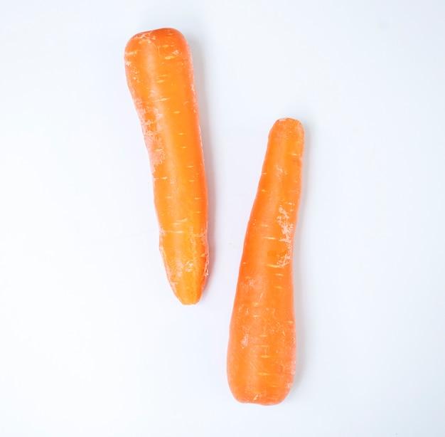 Vista aerea delle carote organiche fresche con priorità bassa bianca