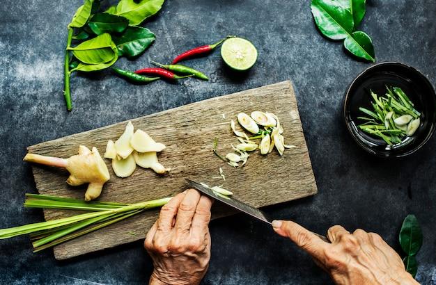 Vista aerea delle mani con erba di limone di taglio del coltello