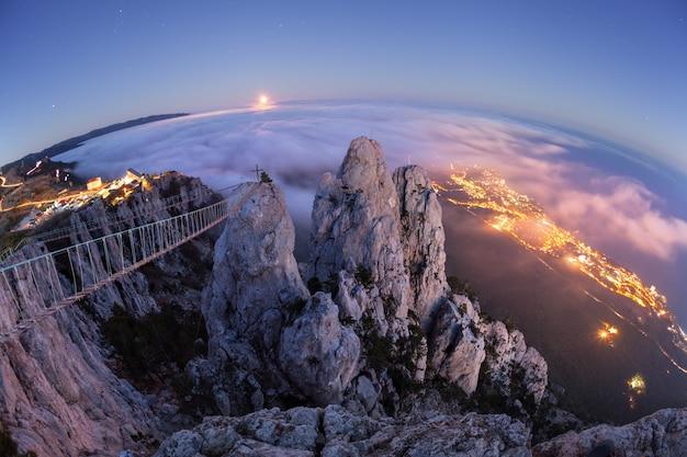 Vista aerea di bello picco di montagna alla notte di estate. abbellisca con la luna piena, il mare, le rocce e le nuvole basse al crepuscolo