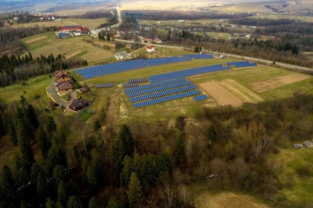 Vista aerea di grande campo del sistema solare dei pannelli fotovoltaici che producono energia pulita rinnovabile su erba verde