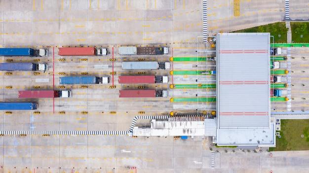 Vista aerea di grandi camion container che entrano con il contenitore di merci attraverso il cancello d'ingresso principale nel porto industriale.