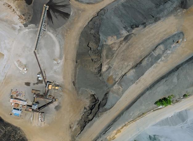 Vista aerea di macchinari pesanti per la frantumazione e la raccolta di materiali di ghiaia di pietra per il riciclaggio e lo stoccaggio di impianti di produttori di asfalto.