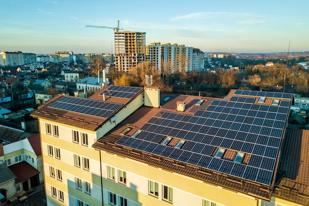 Vista aerea di molti pannelli solari fotovoltaici montati sul tetto del fabbricato industriale.