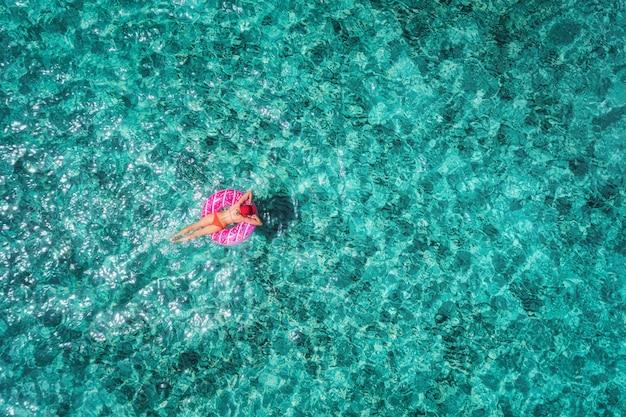 Vista aerea di nuoto esile della giovane donna sull'anello di nuotata della ciambella nel mare blu trasparente al giorno luminoso
