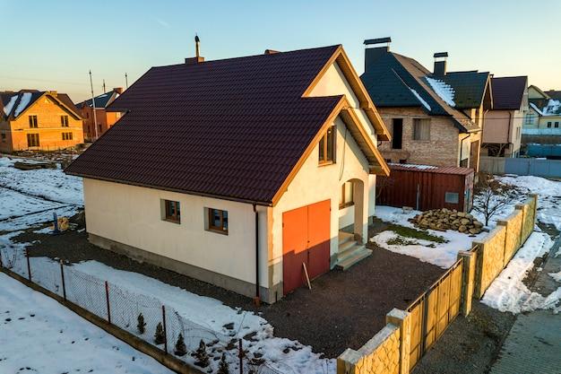 Vista aerea di nuovo cottage residenziale della casa e garage attaccato con il tetto di assicelle sull'iarda recintata il giorno di inverno soleggiato nella zona suburbana moderna. investimento perfetto nella casa dei sogni.