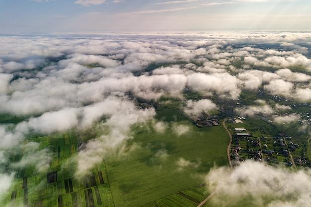 Vista aerea di nuvole bianche sopra una città o un villaggio con file di edifici e strade curve tra campi verdi in estate. paesaggio di campagna dall'alto.