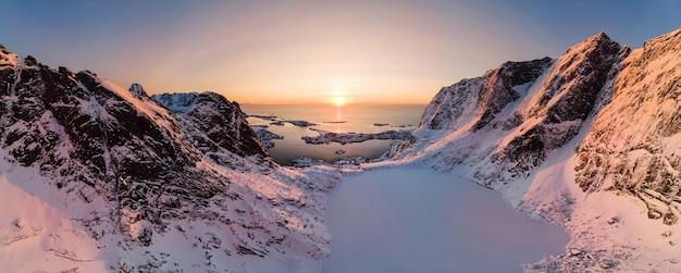 Vista aerea di panorama della catena montuosa con il lago del ghiaccio in valle con l'oceano artico al tramonto