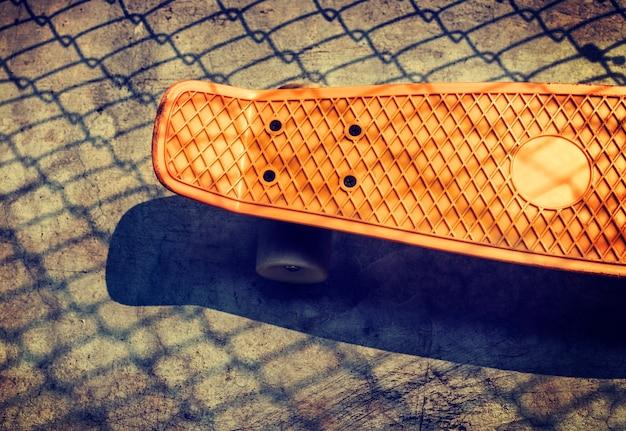 Vista aerea di skateboard arancione a terra