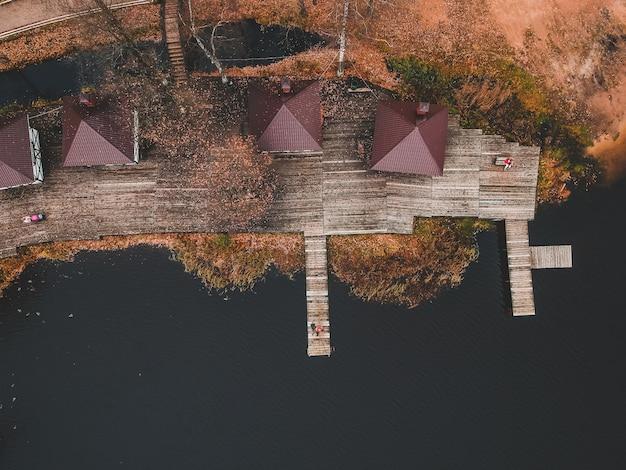 Vista aerea di un pescatore con una canna da pesca sul molo, riva del lago, foresta di autunno. finlandia.