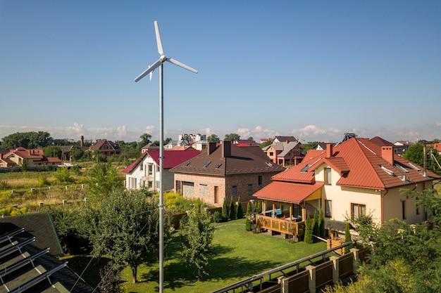 Vista aerea di una nuova casa autonoma con pannelli solari, radiatori di riscaldamento dell'acqua sul tetto e turbina eolica sul cortile verde.
