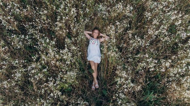 Vista aerea di una ragazza di bellezza che si trova in un giacimento di fiore e nel rilassamento