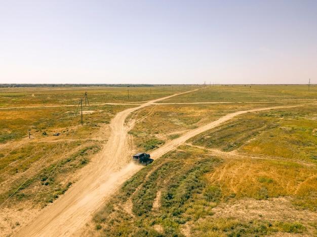 Vista aerea di volo del veicolo fuori strada del camion 4x4 che passa un campo polveroso d