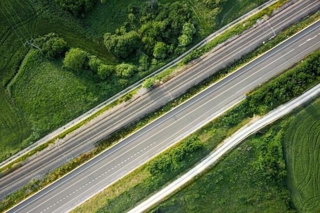 Vista aerea, ferrovia e strada nel paesaggio rurale.